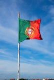 Portugal fahnenschwenkend auf dem Wind über einem bewölkten blauen Himmel lizenzfreie stockfotos
