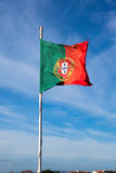Portugal flag waving on the wind over a cloudy blue sky royalty free stock photos