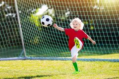 Portugal football fan kids. Children play soccer. Kids play football on outdoor field. Portugal team fans. Children score a goal at soccer game. Boy in royalty free stock photo