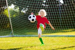 Portugal football fan kids. Children play soccer. Kids play football on outdoor field. Portugal team fans. Children score a goal at soccer game. Boy in royalty free stock images