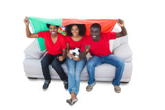 Portugal football fans in red on the sofa Stock Photography