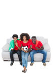 Portugal football fans in red on the sofa Royalty Free Stock Photo