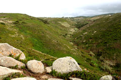 Portugal. Gray stones on green hills on blue sky background, horizontal view. Royalty Free Stock Photos