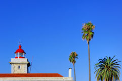 Portugal: Lighthouse on the coast. Portugal, area of Algarve, Lagos: blue sky, palm trees and a nice white Lighthouse on the Atlantic coast stock image