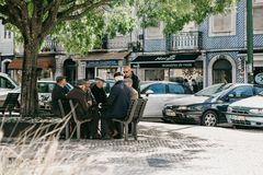Older men locals sit on a bench and communicate in Lisbon in Portugal. Portugal, Lisbon, 01 May 2018: Elderly Portuguese locals sit on the bench and communicate stock images