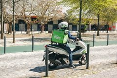 Portugal, Lissabon 29 april 2018: Uber eet arbeider of toerist op motorfiets of bromfiets stock fotografie