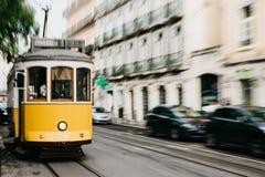 Portugal Lissabon, 01 Juli 2018: En traditionell gul spårvagn för gammalmodig tappning som fortskrider stadsgatan av Lissabon Royaltyfri Bild