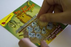Scratching a Lottery Scratchcard with coin stock photos