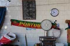 Portugal Scarf, Food Scale, Watch and Price List on White Tile Wall inside Antique Bolhao Market: in Porto, Portugal.  royalty free stock image
