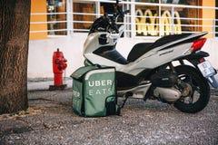 Portugalia, Lisbon 29 2018 Kwiecień: Karmowy doręczeniowy Uber je Motocykl na ziemi i kosz jedzenie który mówi Uber Obraz Stock