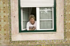 Portugiesische Frau lächelt im Fenster in Lissabon/in Lissabon Portugal Lizenzfreie Stockfotografie