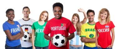 Portugiesischer Fußballfan mit Ball und zujubelnde Gruppe anderer Fans Lizenzfreies Stockfoto