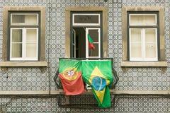 Portugiser och brasilianska flaggor visas från lägenhetbalkong i Lissabon, Lissabon, Portugal, i service av världscupfotboll royaltyfri foto