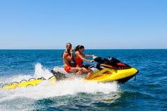 Lifeguards on Jet Ski, Young Couple, Speeding Rescue, Whistling Royalty Free Stock Image