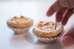 Portuguese Almond Pastry Tart being picked up from a white table. stock photography