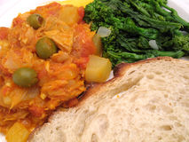 Portuguese Bacalao Dinner. Photo of codfish bacalao with bread and rapini stock images