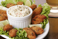 Portuguese cod fish croquettes. Cod fish cakes (croquettes) with chunky tartar sauce.  Typical dish made up of potatoes, bacalhau (codfish), eggs and parsley Royalty Free Stock Images