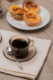 Portuguese Custard Tarts with Coffee. Pasteis de Nata or Portuguese Custard Tarts with black coffee on wooden table Royalty Free Stock Photo
