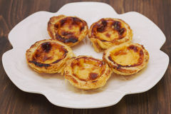 Portuguese dessert pasteis de nata on white dish on brown background Royalty Free Stock Photography