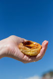 Portuguese dessert Pasteis de nata in women hand. Traditional Portuguese egg tart pasty cake dessert Pasteis de nata in women hand. On background attractions in Stock Images