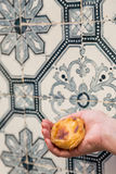 Portuguese dessert Pasteis de nata in women hand. Traditional Portuguese egg tart pasty cake dessert Pasteis de nata in women hand. On background azulejo in Royalty Free Stock Photo