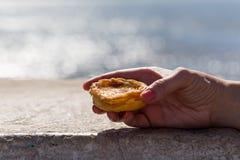 Portuguese dessert Pasteis de nata in women hand Stock Photo