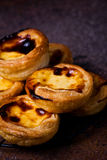 Portuguese Egg Tart. Stacked traditional homemade Portuguese Egg Tarts against dark rustic background stock image
