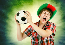 Portuguese fan loudly shouts on the Brazilian colors background Stock Photography