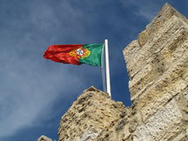 Portuguese Flag. Flying over the Castle of St. Jorge in Lisbon, Portugal against a deep blue sky royalty free stock photography