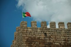 Portuguese flag fluttering on top of tower from Castle. Portuguese flag fluttering on top of stone tower, in a sunny day at the Linhares da Beira Castle. A royalty free stock photos