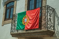 Portuguese flag on iron railing in a balcony from an old building. Portuguese flag on the wrought iron railing of stone balcony in an old building at Linhares da stock photo