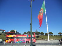 Portuguese flag in Lisbon, Portugal. Big Portuguese flag near Avenida da Libertade with a Sightseeing bus Royalty Free Stock Photo