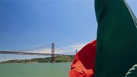 Portuguese flag on a ship on background of 25th April bridge and Jesus statue stock video footage