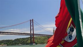 Portuguese flag on a ship on background of 25th April bridge and Jesus statue stock video