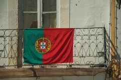Portuguese flag on top of iron handrail of balcony. Portuguese flag on top of wrought iron handrail in an old building balcony on a sunny day at Elvas. A royalty free stock photos