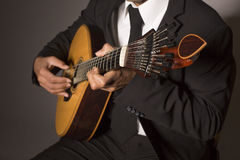 Portuguese guitar. Close up shot of a man with his fingers on the frets of a portuguese guitar playing stock images