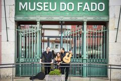 Fado band in front of Fado Museum in Lisbon, Portugal. Portuguese guitar player, fado singer and acoustic guitar player in front of Fado Museum in Lisbon stock image