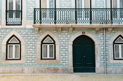 Portuguese house decorated with azulejo. Lisbon, Portugal. Portuguese house with balcony and windows decorated with traditional multicolor portugal ceramics Royalty Free Stock Images
