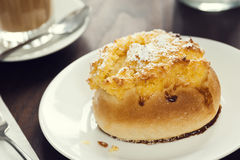 Portuguese Pão de Deus Sweet Roll on Plate in Cafe. A Pão de Deus, a Portuguese sweet roll with a coconut and powdered sugar topping, in a cafe with drinks stock photography