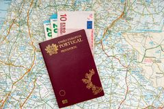 The Portuguese passport and euro banknotes on a geographical map stock photography