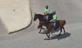 Portuguese policemen on horses. Lagos, Algarve, Portugal - August 16, 2015: Two Portuguese policemen on horses patrolling streets Royalty Free Stock Image