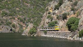 Portuguese railway known as Linha do Douro traveling alongside the river Douro in Portugal. On the narrow tracks carved into the river bank stock video footage