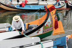Portuguese sailor mooring traditional moliceiro boat in Aveiro,. View daily work of portuguese sailor mooring traditional moliceiro boat, in a canal of Aveiro Royalty Free Stock Image