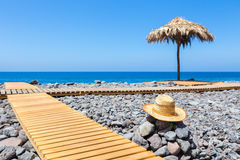 Portuguese stony beach with path sea hat and parasol stock images