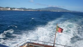 Portuguese Waving Flag in the stern of a ship. View from a boart