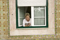 Portuguese woman smiles in window in Lisbon/Lisboa Portugal Royalty Free Stock Photography