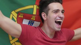 Portuguese Young Man celebrating while holding the flag of Portugal in Slow Motion. High quality stock photo