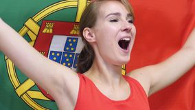 Portuguese Young Woman celebrates holding the flag of Portugal in Slow Motion. High quality stock image