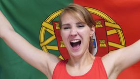 Portuguese Young Woman celebrating while holding the flag of Portugal in Slow Motion. High quality stock photography
