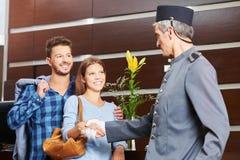 Portvakt som ger handskakningen till par i hotell Royaltyfria Foton